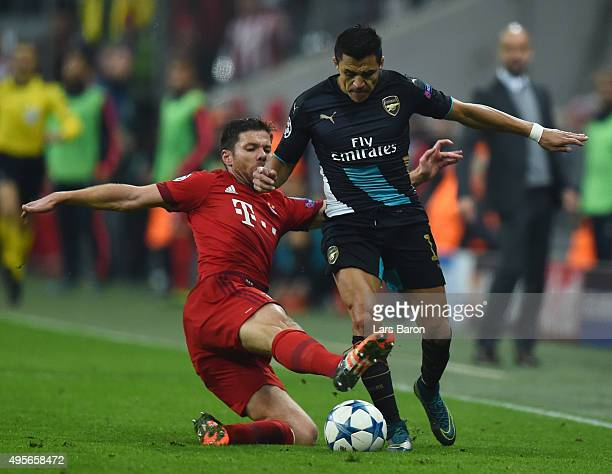 Alexis Sanchez of Arsenal is tackled by Xabi Alonso of Bayern Muenchen during the UEFA Champions League Group F match between FC Bayern Muenchen and...