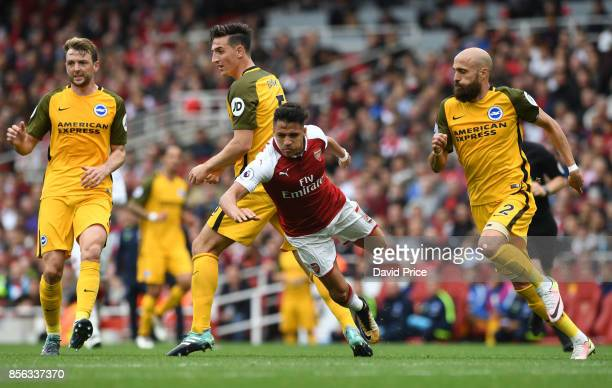 Alexis Sanchez of Arsenal is tripped by Lewis Dunk of Brighton during the Premier League match between Arsenal and Brighton and Hove Albion at...