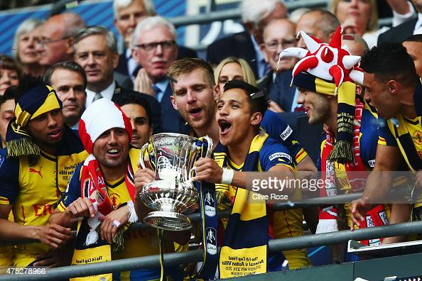 Alexis Sanchez of Arsenal lifts the trophy in celebration after the FA Cup Final between Aston Villa and Arsenal at Wembley Stadium on May 30 2015 in...