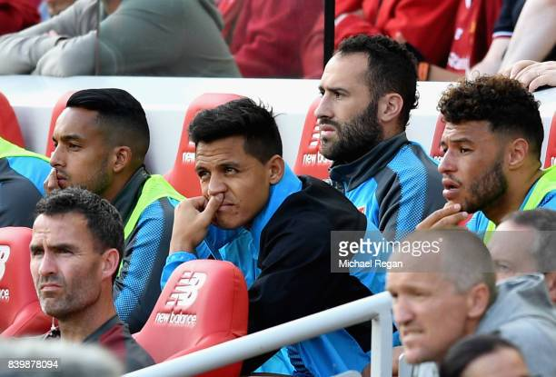 Alexis Sanchez of Arsenal looks on from the bench during the Premier League match between Liverpool and Arsenal at Anfield on August 27 2017 in...