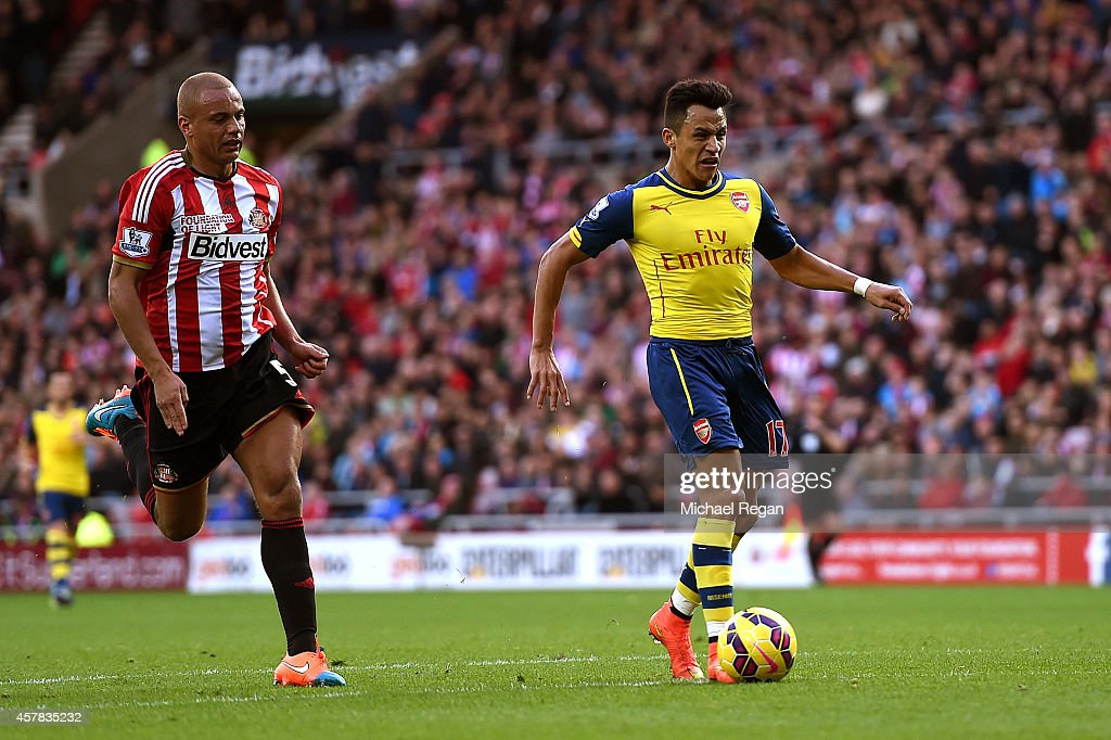 Alexis Sanchez of Arsenal outpaces Wes Brown of Sunderland to score the opening goal during the Barclays Premier League match between Sunderland and Arsenal at the Stadium of Light on October 25, 2014 in Sunderland, England.