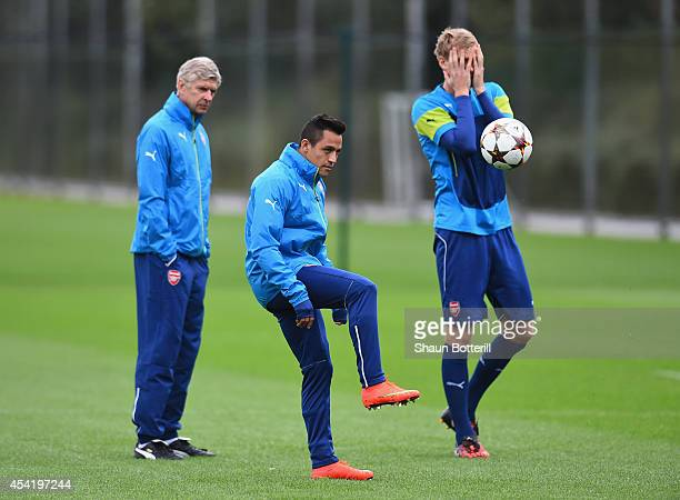 Alexis Sanchez of Arsenal passes the ball as manager Arsene Wenger and Per Mertesacker look on during a training session at London Colney on August...