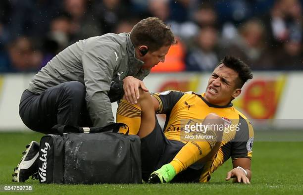 Alexis Sanchez of Arsenal receives treatment from the medical team during the Premier League match between West Bromwich Albion and Arsenal at The...