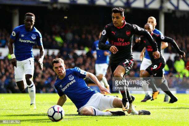 Alexis Sanchez of Arsenal runs past Michael Keane of Everton during the Premier League match between Everton and Arsenal at Goodison Park on October...
