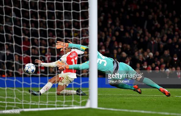 Alexis Sanchez of Arsenal scores his side's third goal past Eduardo of Dinamo Zagreb during the UEFA Champions League match between Arsenal FC and...