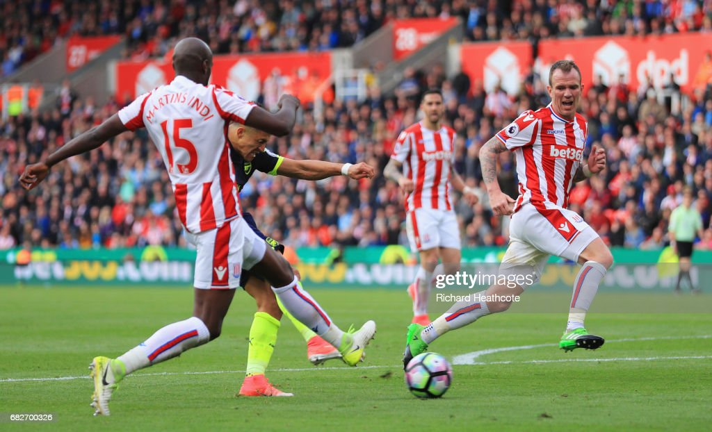 Alexis Sanchez of Arsenal scores his sides third goal while Bruno Martins Indi of Stoke City attempts to block during the Premier League match between Stoke City and Arsenal at Bet365 Stadium on May 13, 2017 in Stoke on Trent, England.