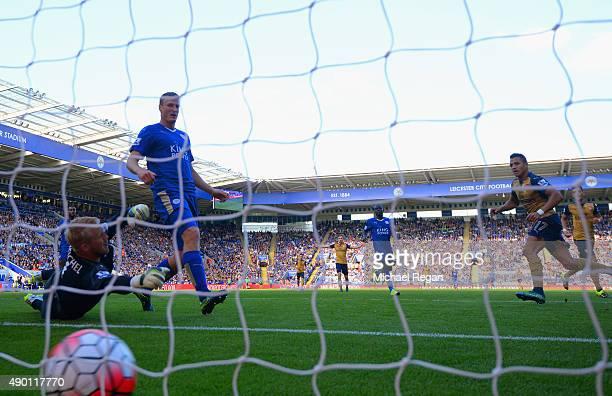 Alexis Sanchez of Arsenal scores his team's second goal past Kasper Schmeichel of Leicester City during the Barclays Premier League match between...