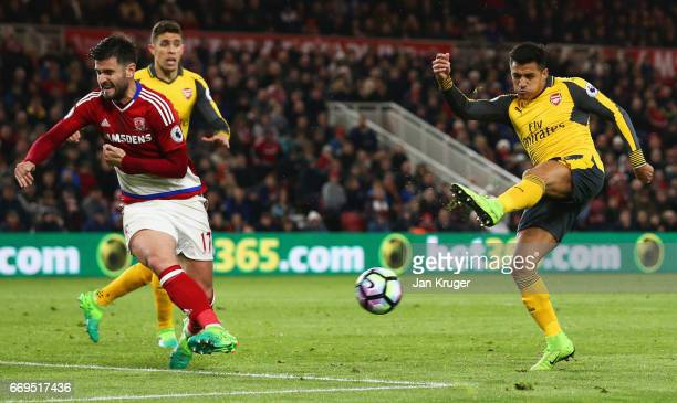 Alexis Sanchez of Arsenal shoots as Antonio Barragan of Middlesbrough attempts to block during the Premier League match between Middlesbrough and...