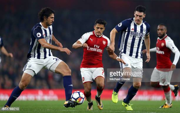 Alexis Sanchez of Arsenal takes on Ahmed ElSayed Hegazi and Gareth Barry of West Bromwich Albion during the Premier League match between Arsenal and...