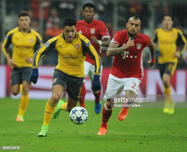 Alexis Sanchez of Arsenal takes on Arturo Vidal of Bayern Munich during the UEFA Champions League Round of 16 first leg match between FC Bayern...