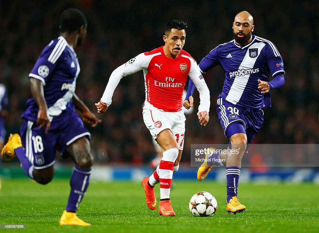 Alexis Sanchez of Arsenal takes on Frank Acheampong and Anthony Vanden Borre of Anderlecht during the UEFA Champions League Group D match between...