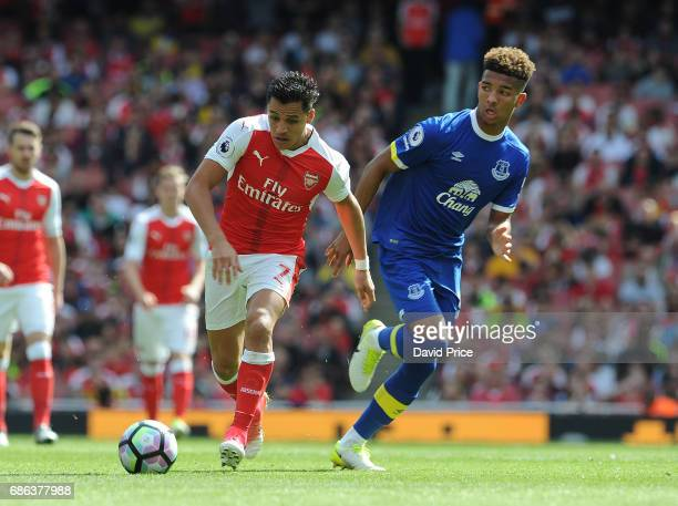 Alexis Sanchez of Arsenal takes on Mason Holgate of Everton during the Premier League match between Arsenal and Everton at Emirates Stadium on May 21...