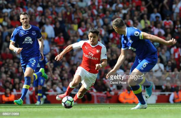 Alexis Sanchez of Arsenal takes on Morgan Schneiderlin and Phil Jagielka of Everton during the Premier League match between Arsenal and Everton at...