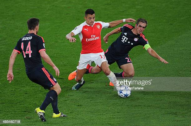 Alexis Sanchez of Arsenal takes on Philipp Lahm and Xabi Alonso of Bayern Munich during the UEFA Champions League match between Arsenal and Bayern...