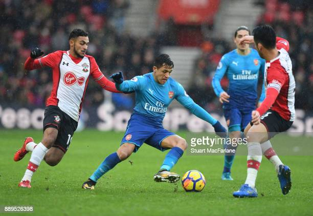 Alexis Sanchez of Arsenal takes on Sofiane Boufal and Maya Yoshida of Southampton during the Premier League match between Southampton and Arsenal at...