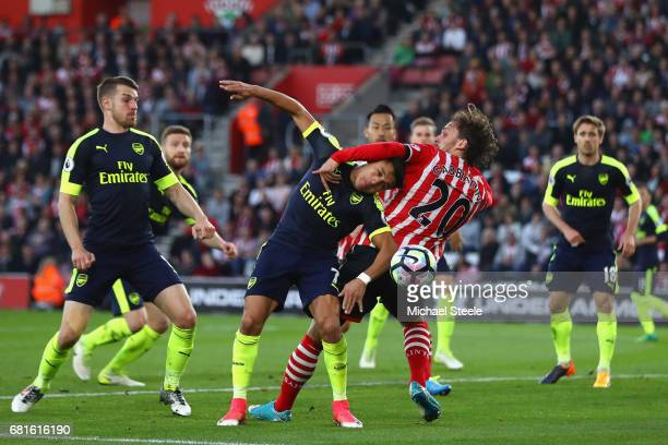 Alexis Sanchez of Arsenal tangles with Manolo Gabbiadini of Southampton during the Premier League match between Southampton and Arsenal at St Mary's...