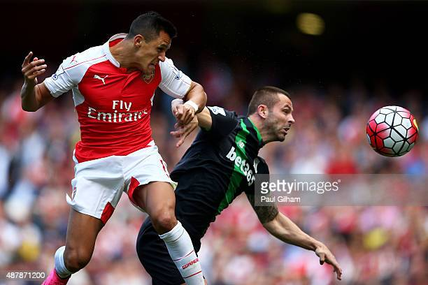 Alexis Sanchez of Arsenal wins a header from Phil Bardsley of Stoke City during the Barclays Premier League match between Arsenal and Stoke City at...