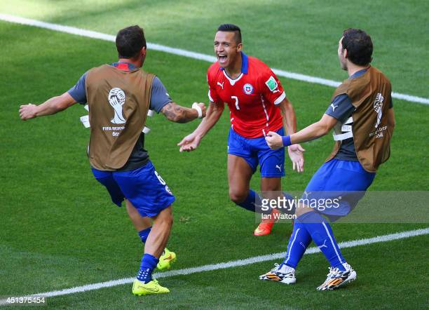 Alexis Sanchez of Chile celebrates scoring his team's first goal with teammates during the 2014 FIFA World Cup Brazil round of 16 match between...