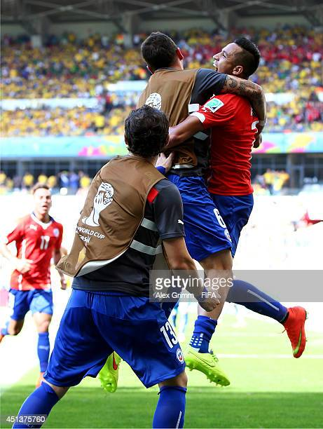 Alexis Sanchez of Chile celebrates scoring his team's first goal with his teammates Carlos Carmona and Jose Rojas during the 2014 FIFA World Cup...