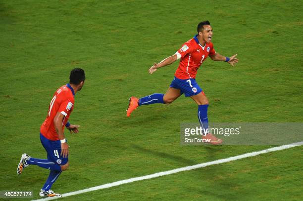 Alexis Sanchez of Chile celebrates scoring the team's first goal with Mauricio Isla during the 2014 FIFA World Cup Brazil Group B match between Chile...