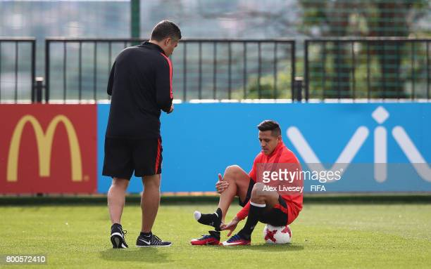 Alexis Sanchez of Chile changes his footwear during a training session at the Strogino Training Ground during the FIFA Confederations Cup Russia 2017...