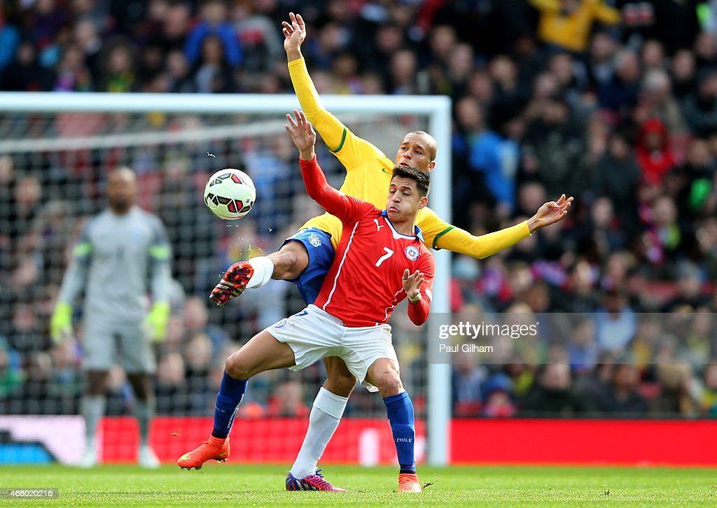 Alexis Sanchez of Chile is tackled by Miranda of Brazil during the international friendly match between Brazil and Chile at the Emirates Stadium on...