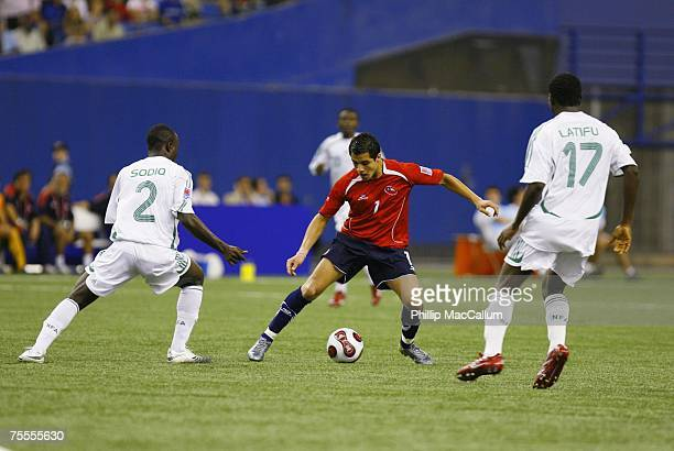 Alexis Sanchez of Chile plays the ball as Suraj Sodiq and Akeem Latifu of Nigeria defend during the Quaterfinal match of the FIFA U20 2007 World Cup...