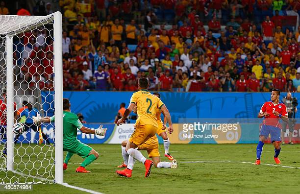 Alexis Sanchez of Chile shoots and scores against goalkeeper Mathew Ryan of Australia during the 2014 FIFA World Cup Brazil Group B match between...