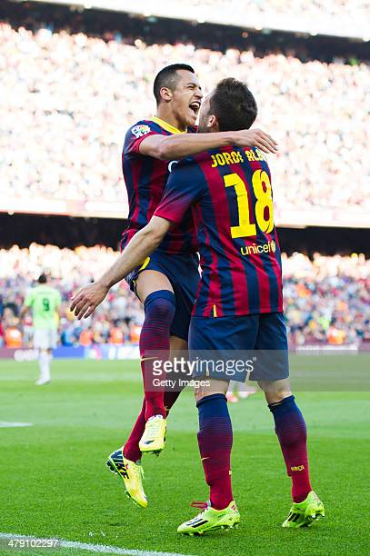 Alexis Sanchez of FC Barcelona celebrates with his teammate Jordi Alba after scoring his team's second goal during the La Liga match between FC...