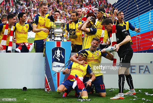 Alexis Sanchez Olivier Giroud and Wojciech Szczesny of Arsenal celebrate with the trophy and champagne after the FA Cup Final between Aston Villa and...