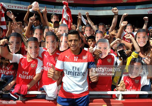 Alexis Sanchez poses with Arsenal fans after a training session at Emirates Stadium on August 7 2014 in London England