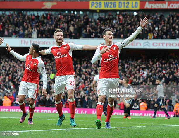 Alexis Sanchez Shkodran Mustafi and Laurent Koscielny celebrate the Arsenal goal during the Premier League match between Arsenal and Tottenham...