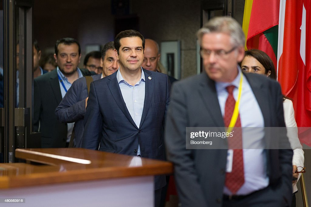 Alexis Tsipras Greece's prime minister center reacts as with Euclid Tsakalotos Greece's finance minister center left walks behind as they depart...