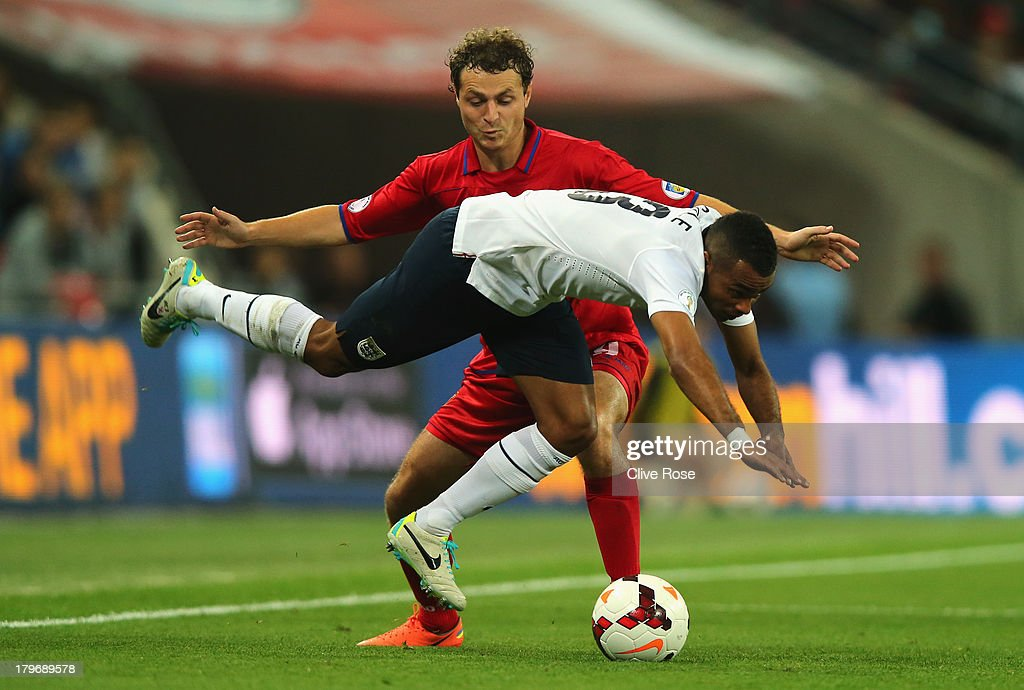 Alexsandru Antoniuc of Moldova (back) challenges Ashley Cole of England during the FIFA 2014 World Cup Qualifying Group H match between England and Moldova at Wembley Stadium on September 6, 2013 in London, England.