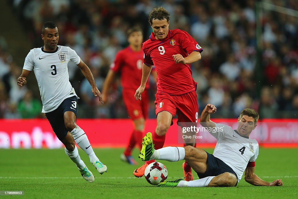 Alexsandru Antoniuc (C) of Moldova is tackled by Steven Gerrard of England as Ashley Cole of England (L) chases during the FIFA 2014 World Cup Qualifying Group H match between England and Moldova at Wembley Stadium on September 6, 2013 in London, England.
