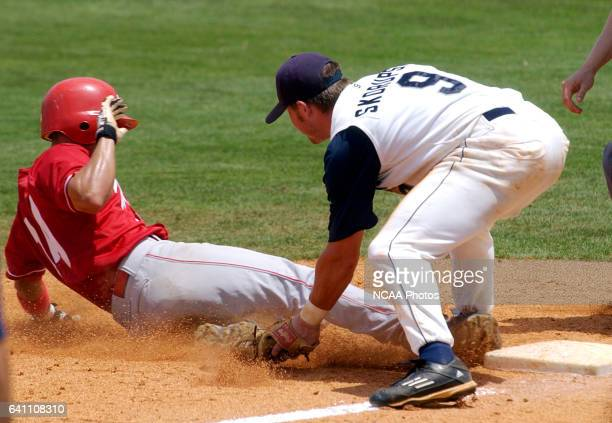 Alexy Hernandez of Florida Southern slides safely between the feet of North Florida's Jon Skorupski after hitting a triple in the seventh inning...