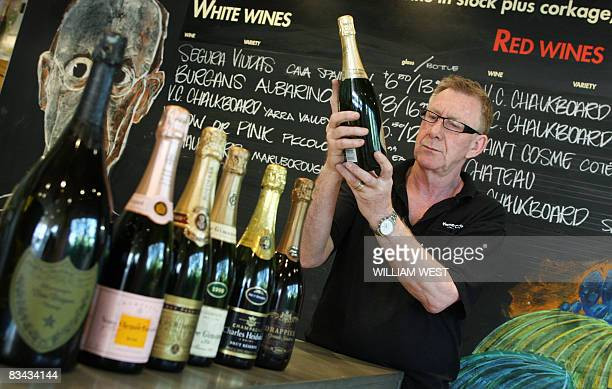 Alf Frankland of Vintage Cellars in the upmarket Melbourne suburb of South Yarra inspects a bottle of French champagne on October 24 as a plunge in...