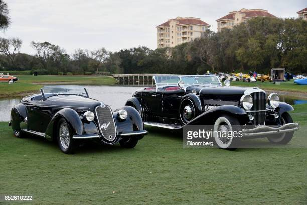 Alfa Romeo Automobiles SpA 8C 2900 convertible touring vehicle left and a 1939 Dusenberg Model SJ convertible luxury vehicle sit on display during...