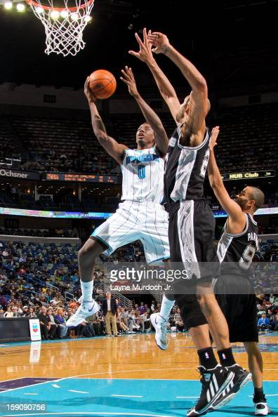 AlFarouq Aminu of the New Orleans Hornets drives to the basket against Tony Parker and Tim Duncan of the San Antonio Spurs on January 7 2013 at the...