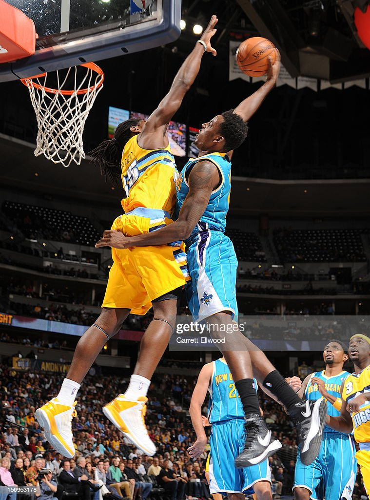Al-Farouq Aminu #0 of the New Orleans Hornets goes to the basket against Kenneth Faried #35 of the Denver Nuggets during the game between the New Orleans Hornets and the Denver Nuggets on November 25, 2012 at the Pepsi Center in Denver, Colorado.