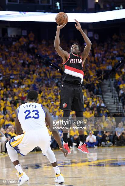 AlFarouq Aminu of the Portland Trail Blazers shoots over Draymond Green of the Golden State Warriors in the fourth quarter during Game One of the...