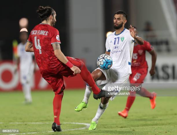 AlFateh's player Abdelkader Oueslati fights for the ball against Lekhwiya's Chico Flores during the AFC Champions League football match between...