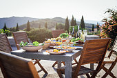 A horizontal image of a typical outdoor Mediterranean meal, there is a beautiful landscape of Tuscany, Italy, in the background. There are no people in the shot.