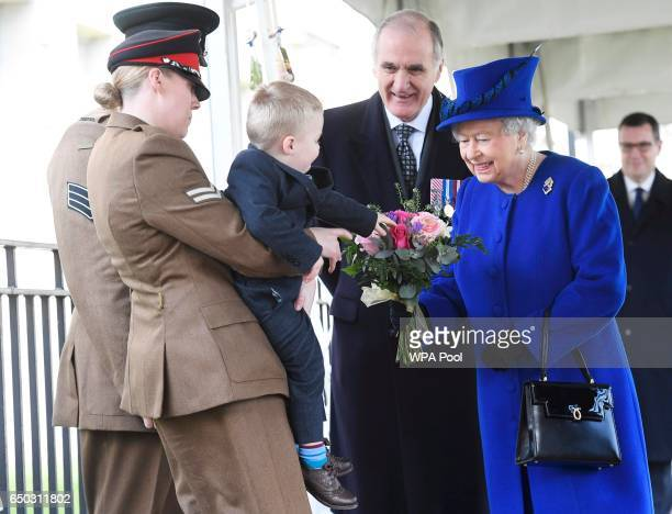 Alfie Lun is held up by his mother Michelle as he hands a bouquet to Queen Elizabeth II during the unveiling of the new memorial to members of the...