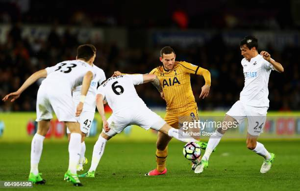 Alfie Mawson of Swansea City and Jack Cork of Swansea City attempt to tackle Vincent Janssen of Tottenham Hotspur during the Premier League match...