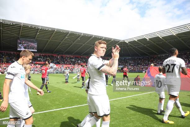 Alfie Mawson of Swansea City applauds the home fans prior to kick off of the Premier League match between Swansea City and Manchester United at The...