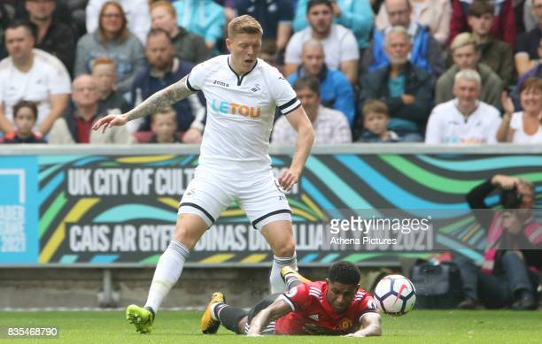 Alfie Mawson of Swansea City challenges Marcus Rashford of Manchester United during the Premier League match between Swansea City and Manchester...