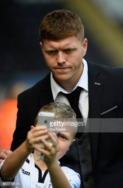 Alfie Mawson of Swansea City has a photo taken with a fan as he arrives at the stadium prior to the Premier League match between Swansea City and...