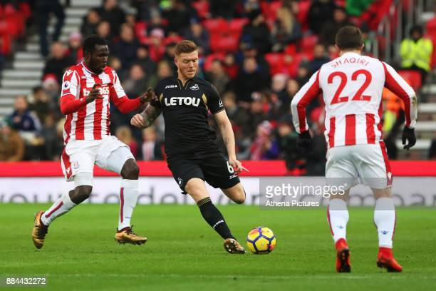 Alfie Mawson of Swansea City is challenged by Kurt Zouma of Stoke City during the Premier League match between Stoke City and Swansea City at the...
