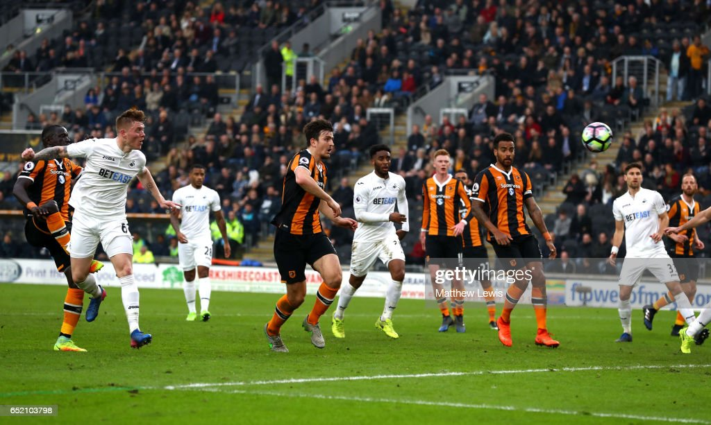 Alfie Mawson of Swansea City (L) scores their first goal during the Premier League match between Hull City and Swansea City at KCOM Stadium on March 11, 2017 in Hull, England.